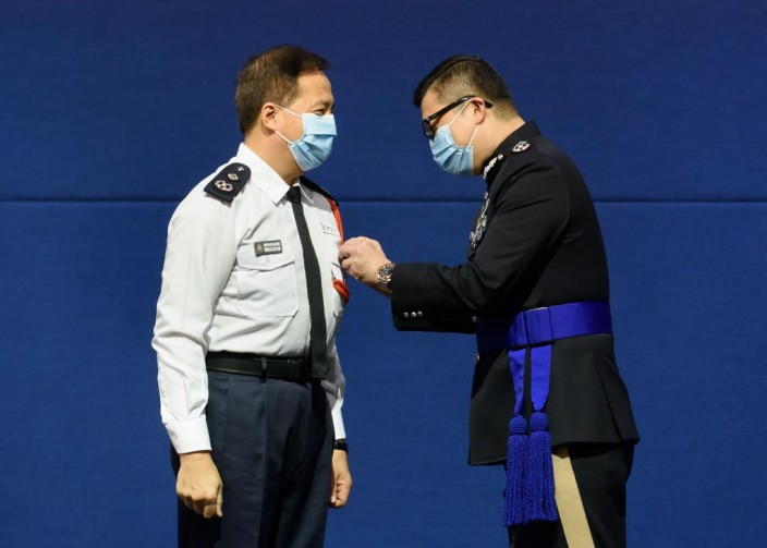 警務處處長鄧炳強(右)向參與特別行動的人員,頒授「香港警察特別行動獎章」。