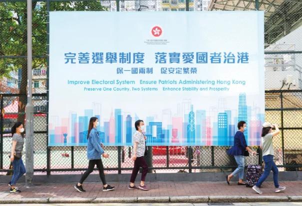 """2021年3月31日,香港市民從旺角街頭的""""完善選舉制度 落實愛國者治港""""看板前經過。隨著全國人大通過有關完善特區選舉制度的決定和全國人大常委會修訂香港基本法附件一和附件二,香港特區政府在全港多個地方設置大型戶外廣告,宣傳""""完善選舉制度 落實愛國者治港""""。"""