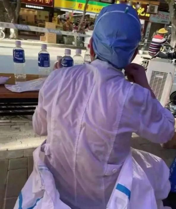 21日下午,一張照片在網上瘋傳——在荔灣區錦龍社區核酸檢測站,一名護士的白大褂被汗水完全浸濕。濕到什麼程度?估計能擰出半斤水來。