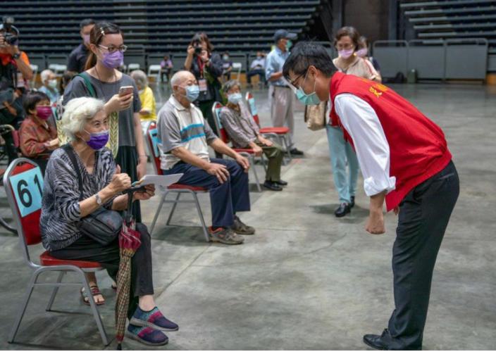 高雄市長陳其邁15日一天三度到巨蛋體育館視察接種站情況,也與長輩寒暄問候。