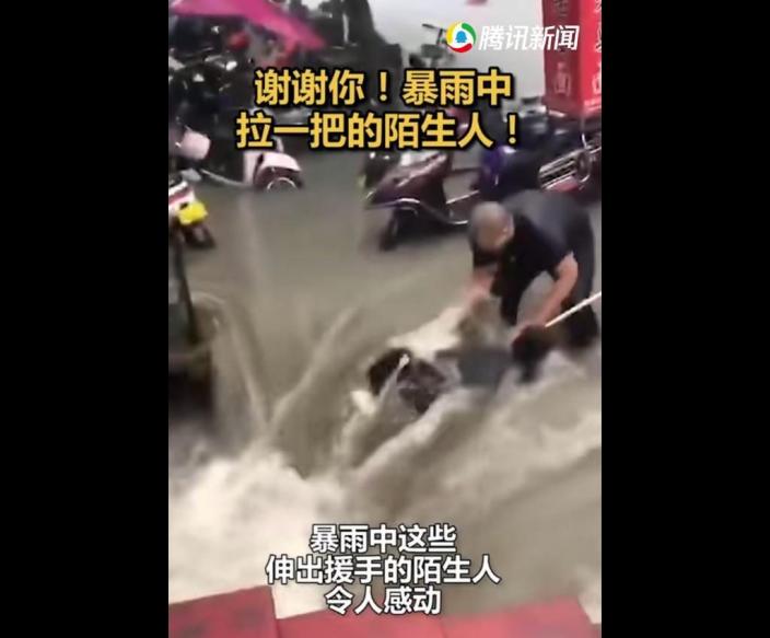 民眾在洪水中搶救被沖走的人。