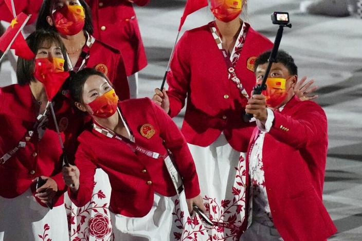 中國代表隊身穿「開門紅」主題禮服入場。AP圖片