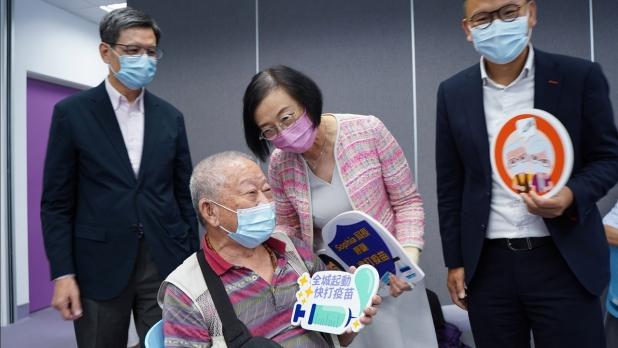 陳肇始到訪葵青地區康健中心,了解中心與地區網絡醫生合作舉辦的新冠疫苗外展接種服務。(政府新聞處)