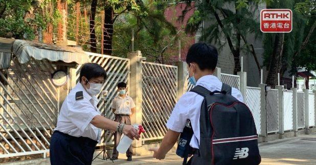 校方在校門設置體溫監測儀,派人為進入學校的學生噴灑消毒液清潔雙手。(陳曉筠攝)